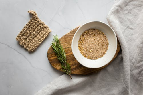 Washcloth composed with organic scrub and branch of rosemary