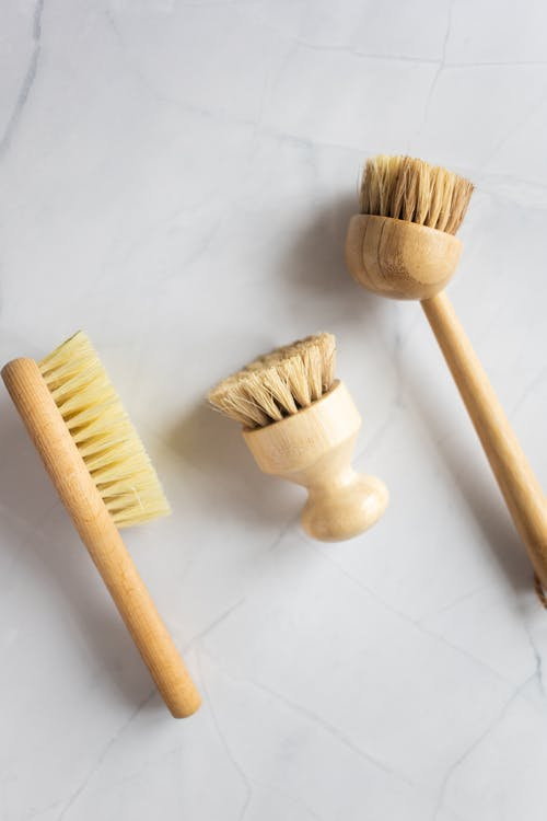 Top view of organic wooden brushes for spa procedures and cleaning on white background