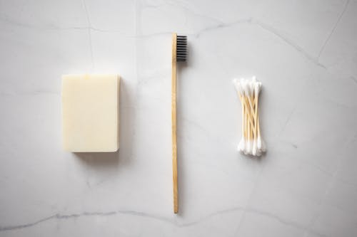 From above of bamboo toothbrush placed between organic soap and wooden ear sticks placed on marble table