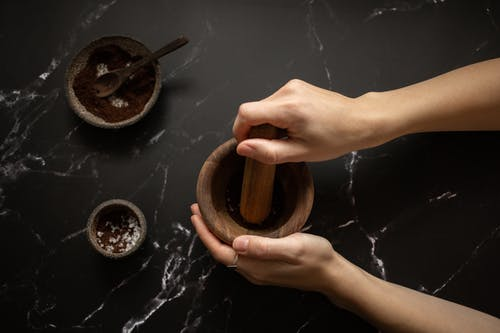 From above of crop unrecognizable female using pestle while grinding fresh aromatic coffee in mortar on black marble table