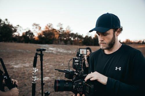 Man in Blue Crew Neck T-shirt Holding Black Dslr Camera
