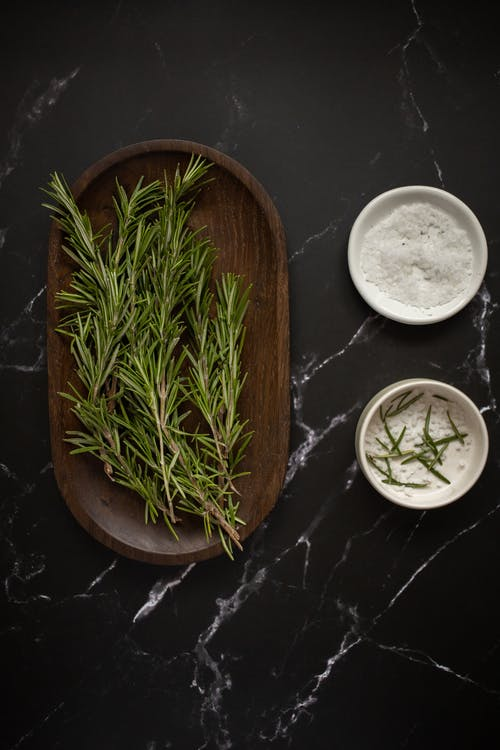 Fresh rosemary placed near small bowls with salt
