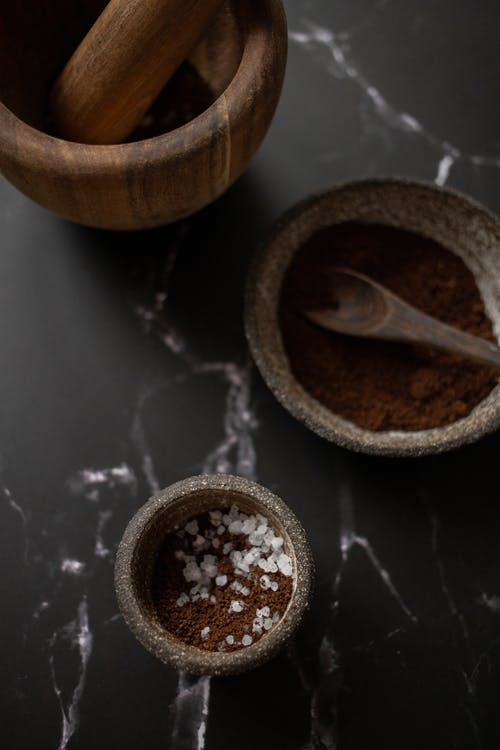 Ceramic bowls with coffee placed near mortar and pestle on table