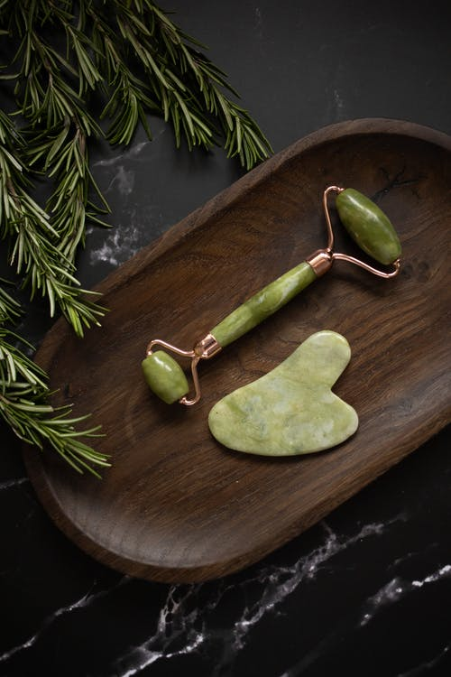 From above of Jade roller and Gua Sha massage tool placed on wooden plate on black marble table with fresh twigs of rosemary