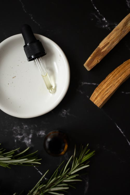 Top view of white clean plate with aromatic oil composed with timber sticks and fresh verdant branches of rosemary