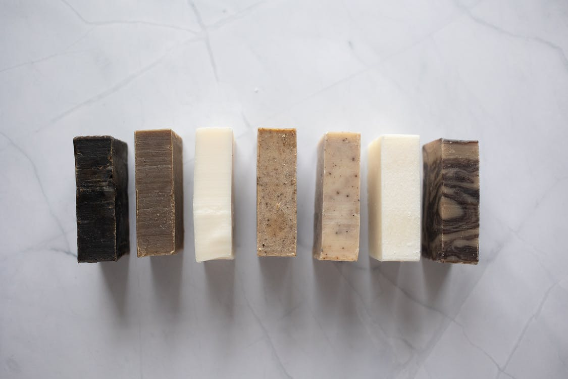 Collection of natural soaps placed on marble table