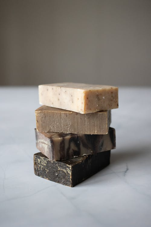 Pile of handmade organic soaps placed in white marble table against blurred background