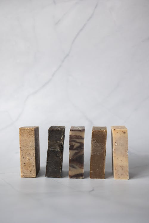 Set of handmade organic soaps placed in row against light marble background in studio