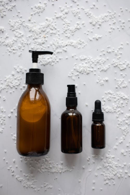 High angle of various bottles of moisturizing cosmetic products placed on white table with salt grains