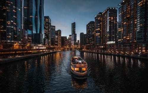 Boat on Water Near City Buildings during Night Time