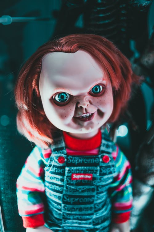 Creative design of doll with redhead and freckles on terrible face representing aggressive character at home