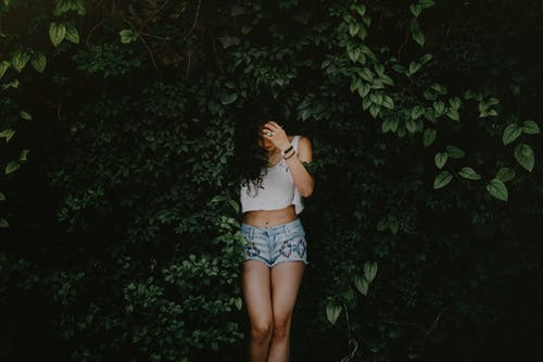 Woman in White Tank Top and Blue Denim Shorts Standing Beside Green Leaves