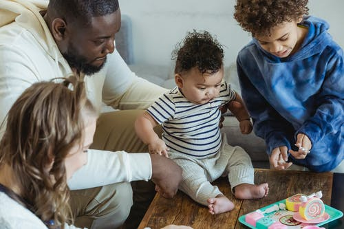 From above of crop multiethnic parents with children playing at table on weekend at home