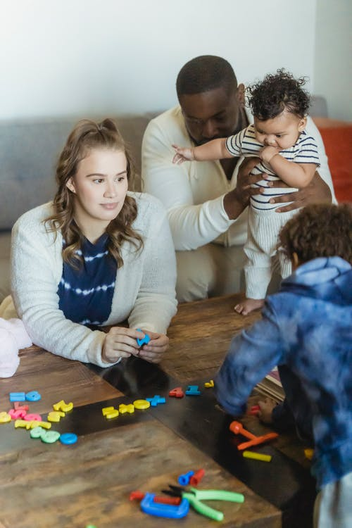 Unrecognizable multiracial family playing at table in room