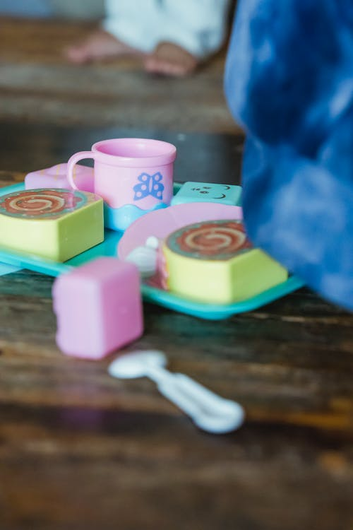Bright plastic toy set with small mug and rolls with spoon on wooden desk against faceless toddler child