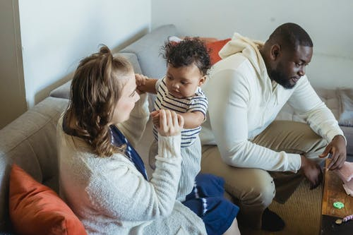 Cheerful multiethnic family spending time on sofa at home