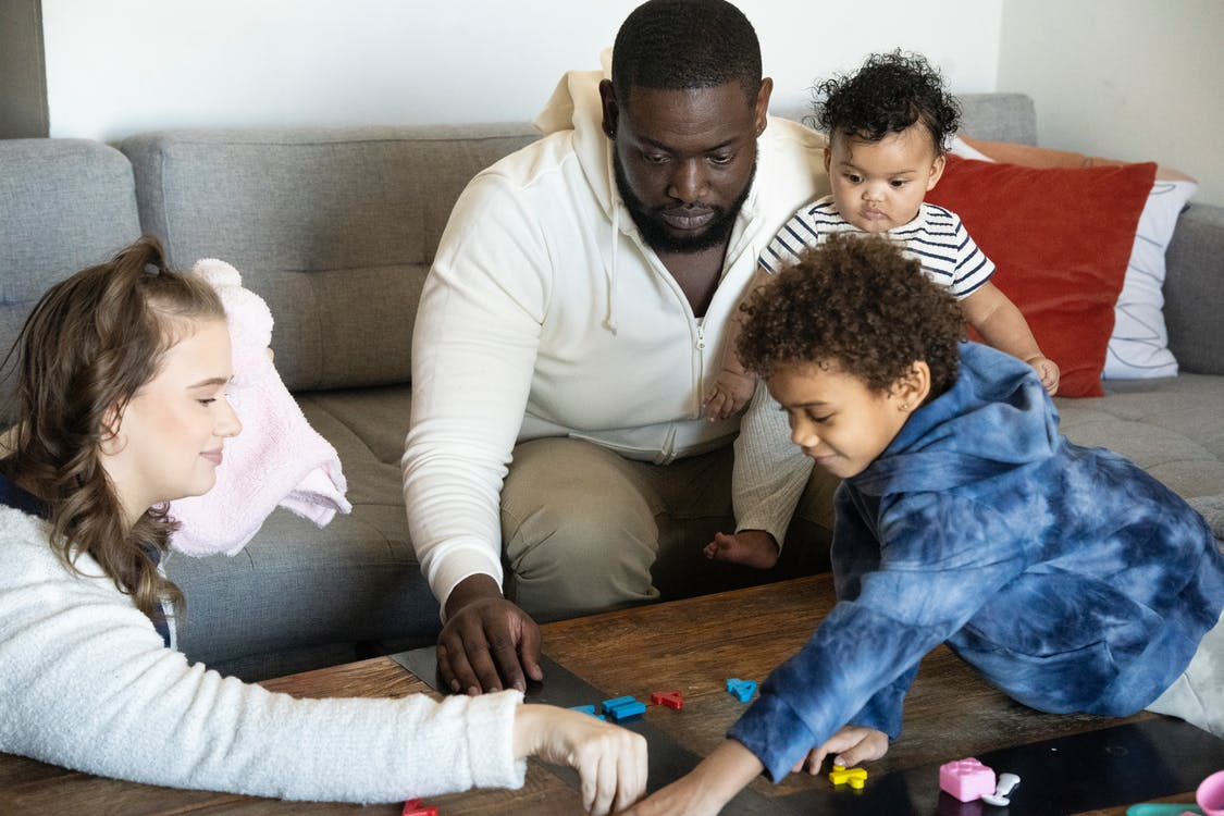 Crop multiethnic parents with children playing with toy numbers on sofa in house room