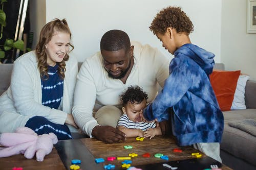Happy multiracial family playing with little cute baby at table with colorful toys at home