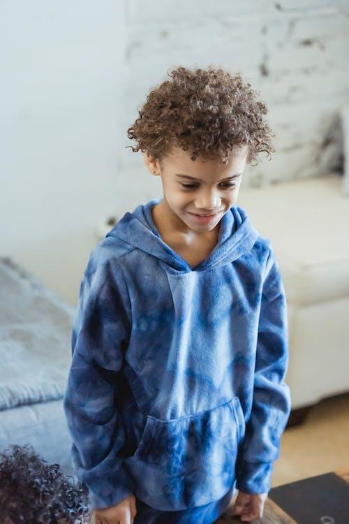 Happy black boy in trendy blue hoodie