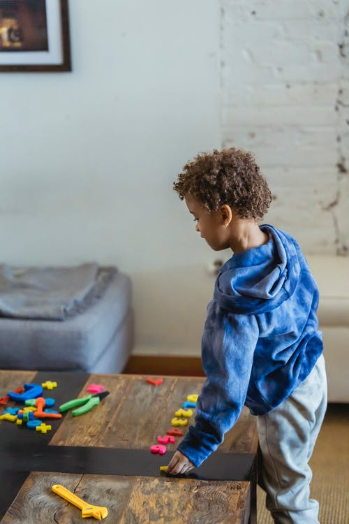 High angle side view of African American child placing toy numbers in row while standing at wooden table at home