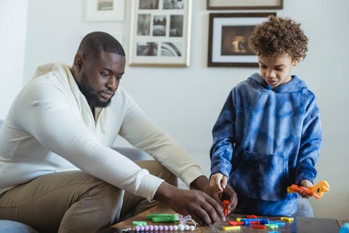 Serious African American father helping curly haired son during game with toy instruments at home