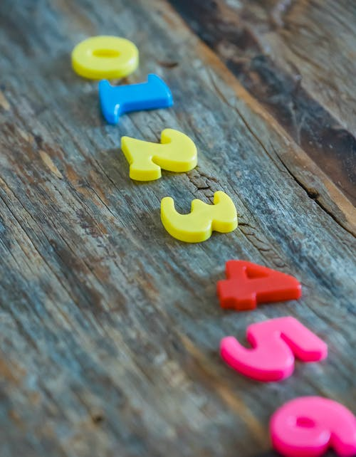 Multicolored numbers for counting on wooden table