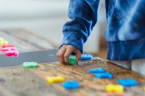 Crop anonymous ethnic boy taking plastic number from wooden table while learning math