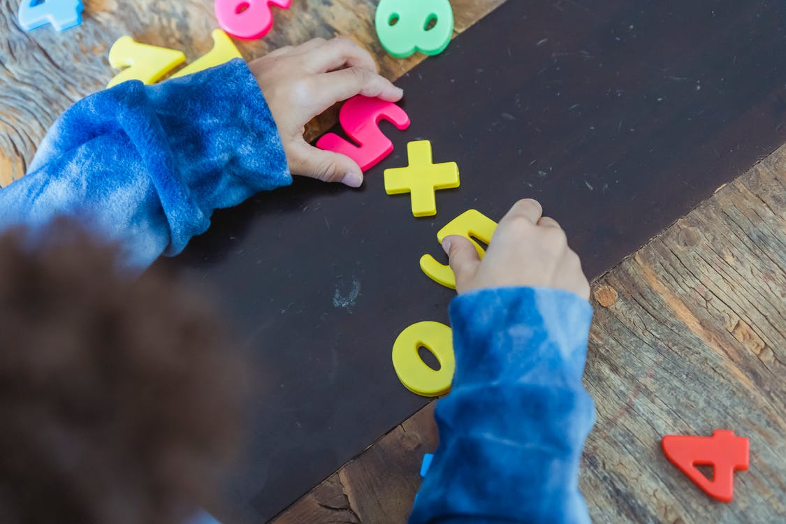 Ethnic boy solving mathematical example made of toy numbers