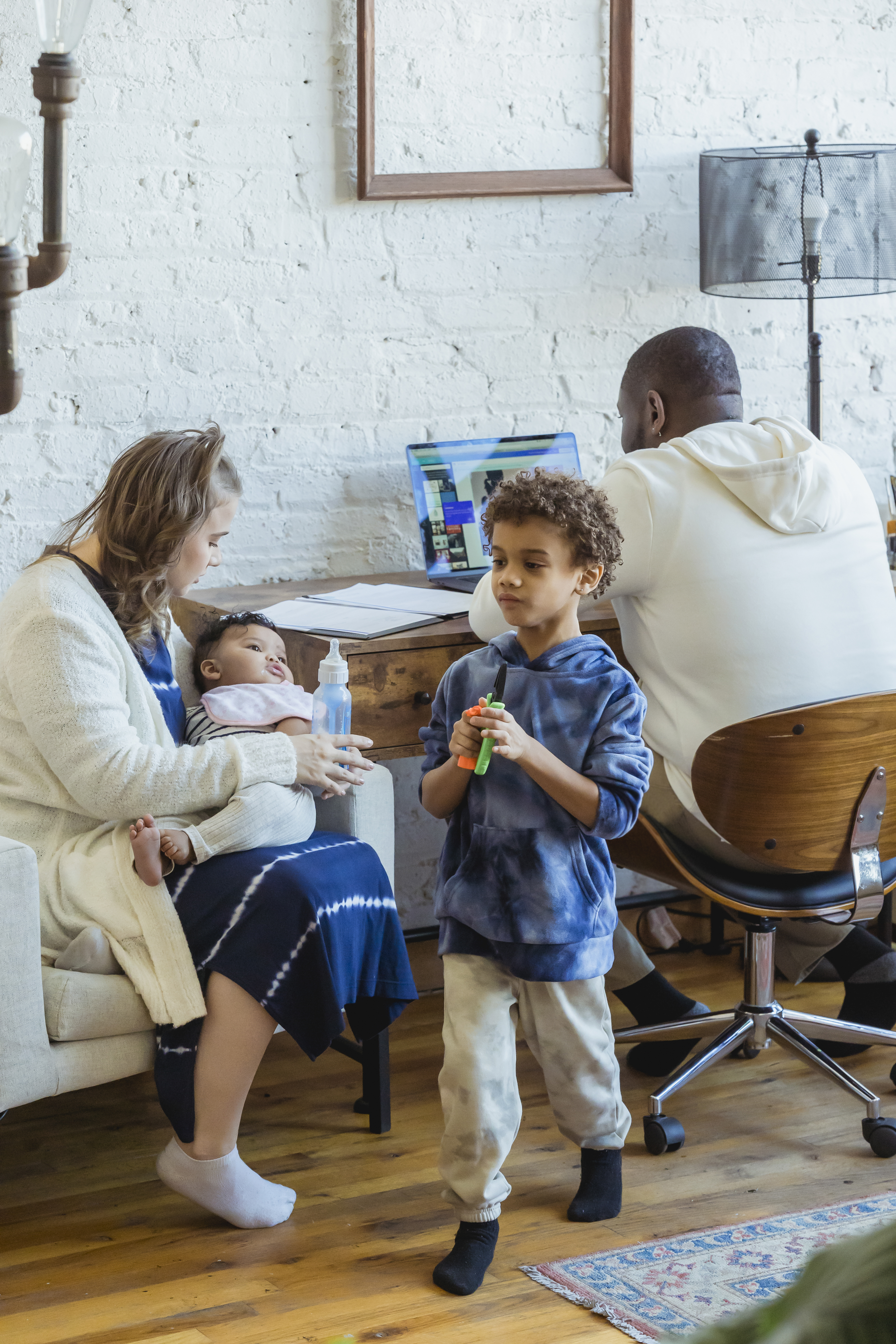 black father working on laptop near kids and mother