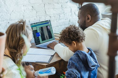 High angle of African American dad watching laptop working near son playing toys and mother feeding little infant