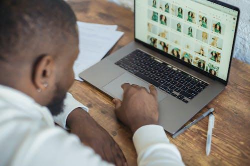 Black man surfing laptop during online work