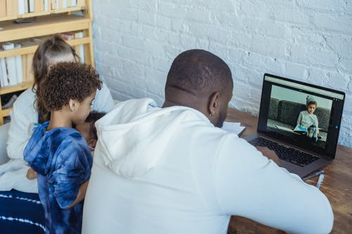 High angle of African American male remote worker surfing netbook while working from home with son mother and baby