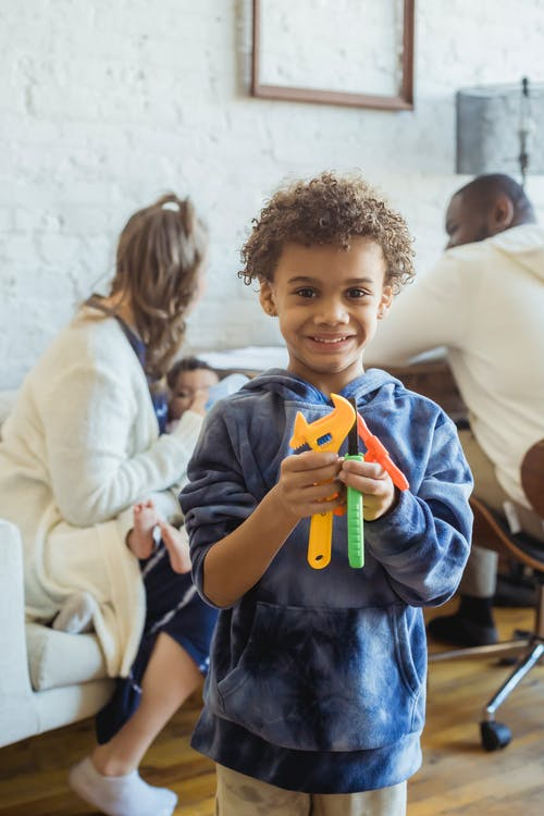 Happy African American boy with toy tools looking at camera while standing in room with multiracial parents and small baby