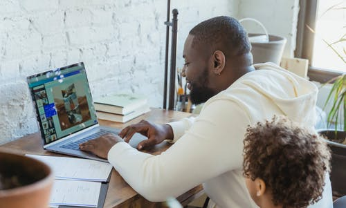 Side view of cheerful African American father browsing netbook while sitting at table near black son in living room at home