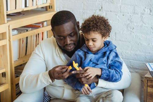 Curious African American father and black son with toy wrench sitting near shelves while playing in light room at home