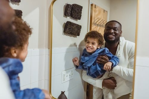 Content African American father with son in hands looking at reflection of mirror and showing teeth while standing in bathroom