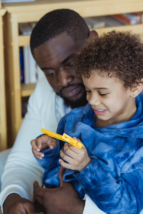 Black father with son playing with toy adjustable wrench