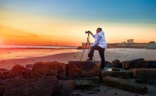 Man in White T-shirt and Blue Denim Jeans Holding Camera on Tripod on Beach during