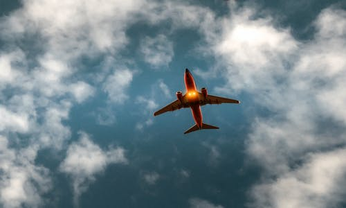 Orange and White Airplane Under Blue Sky and White Clouds