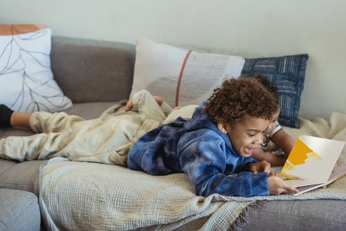 Boy in Blue Jacket Lying on Bed