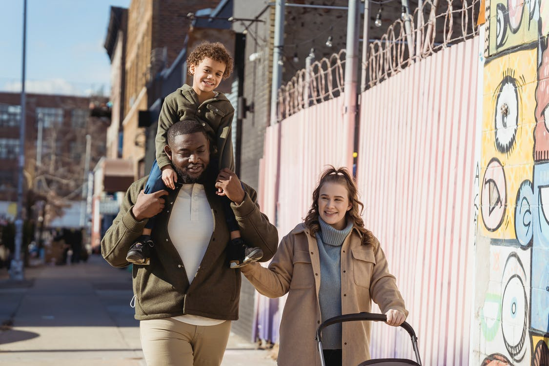 Positive African American father with son on shoulders and happy mother with baby stroller strolling on sunny street in city