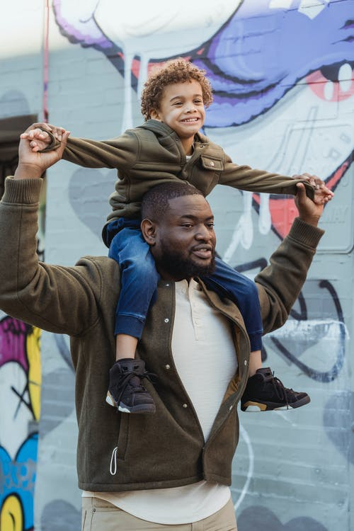 Cheerful black father with son on shoulders