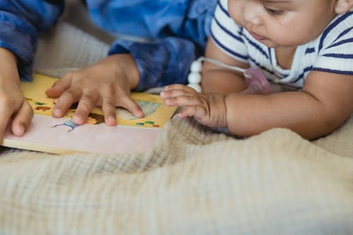 Child in White and Black Stripe Tank Top Lying on Bed