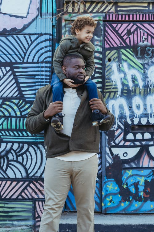 Positive African American father with son on shoulders looking away while standing near colorful wall with street art in city