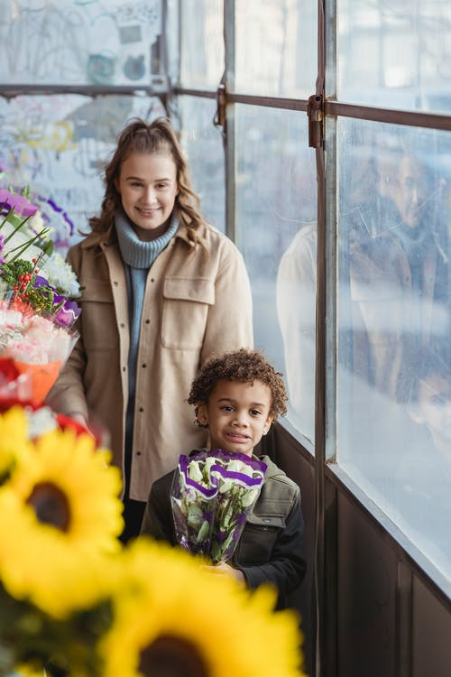Positive mother with black son in flower shop