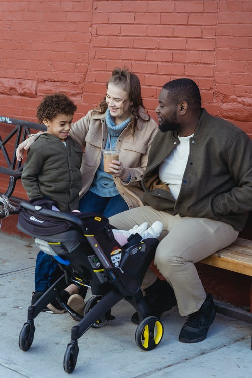 Multiethnic family with baby stroller on street