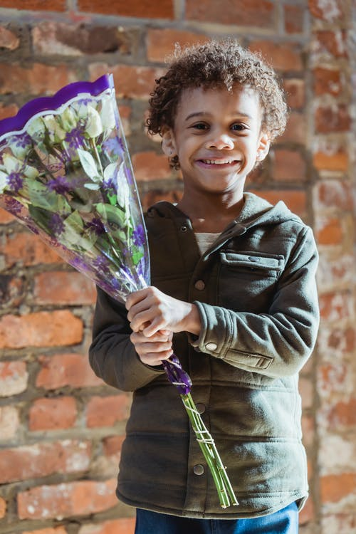 Happy cute African American boy in casual clothes holding bouquet of fragrant white flowers and looking at camera with smile while standing against shabby brick wall