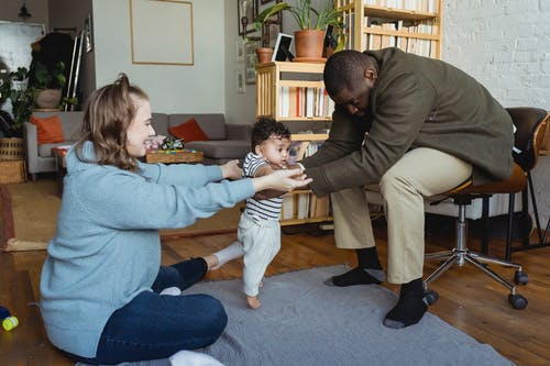 Side view full body of cheerful mom holding hands of African American infant learning walking toward dad