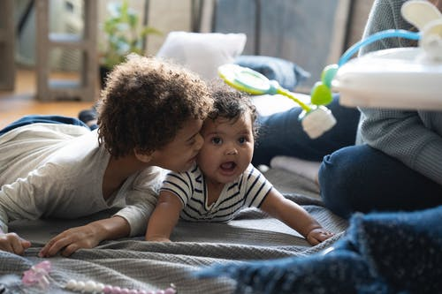 Cute black boy kissing baby with mouth opened