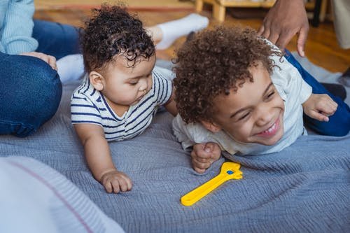 Crop African American dad tickling laughing son lying on floor near curious baby near mother